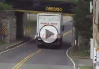 A 12-foot 6-inch tall truck hits a train bridge and sheers the top off!